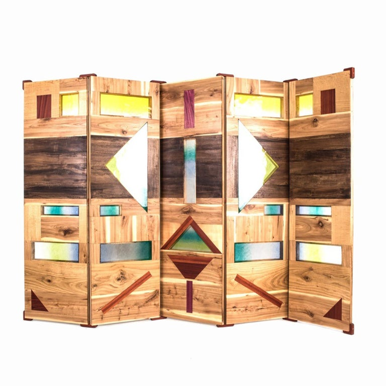 """The screen cover """"Light tropics"""" represents a mask which is inspired by a group of indigenous people called the Caduvei. The screen stylizes face painting by using colorful elements like burnt Murano glass and naturally colored woods from Brazil."""
