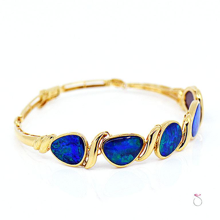 Absolutely stunning 14k yellow gold black Australian lightning ridge Opal bracelet. This gorgeous bracelet is beautifully crafted in 14K yellow gold and set with five large Australian lightning ridge opals. The stunning Opals displays a beautiful