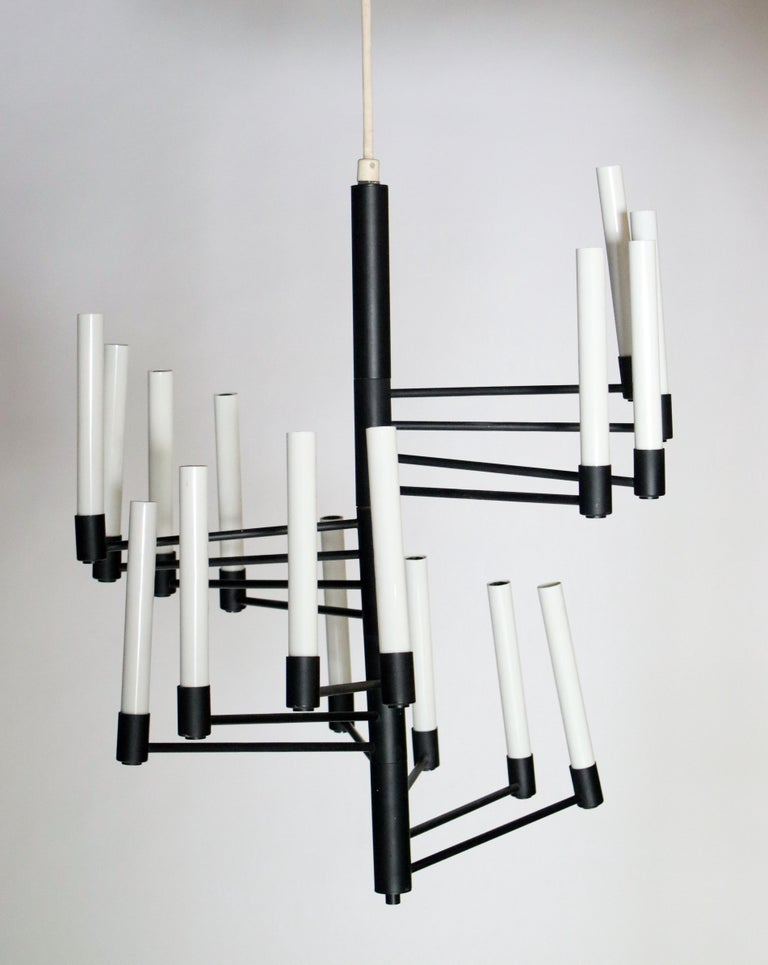 Black metal with white candles chandelier features 16 adjustable lights. Labelled