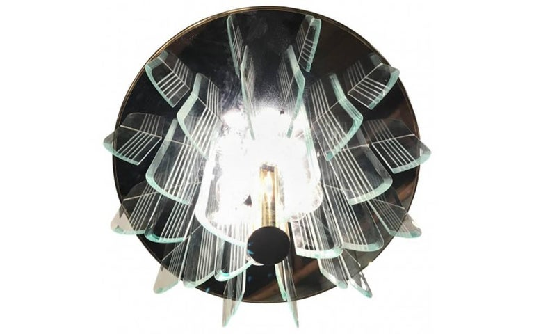 This large and modern chandelier is reminiscent of an opulent Art Deco style. With twelve lights, this imposing fixture is made with etched glass plates for an extraordinary effect.