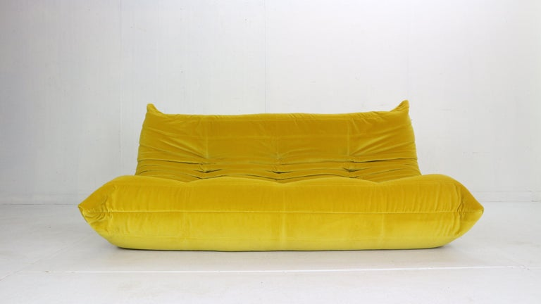 Magnificent Togo three seater lounge sofa designed by Michel Ducaroy in 1973 and was manufactured by Ligne Roset in France. Very comfortable and beautiful accent to your living room space. It has been newly reupholstered in a yellow soft velvet