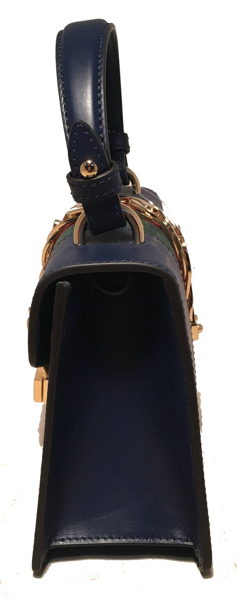 Gucci Navy Blue Leather Sylvie Mini Handbag with Strap in new excellent condition. Navy blue leather exterior trimmed with gold hardware and signature red and green striped canvas center. Unique buckle front closure opens to a beige suede interior