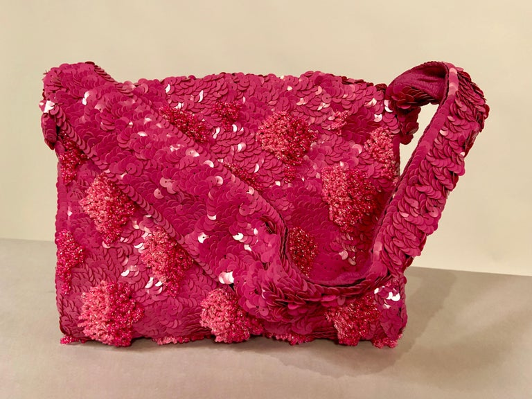 Lilac sequins are sewn in a circular pattern on  to to liac silk crepe. This is then rebeaded with loops of caviar beads in shades of lilac to pale pink in a floral or grape cluster motif. The bag has a wide beaded top handle, and a hinged opening.