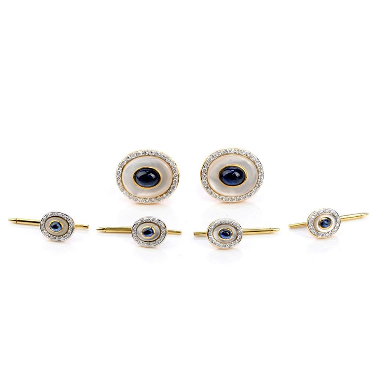 This elegant 18K yellow gold men's tuxedo cufflink set is adorned with sparkling diamonds, blue sapphires and mother of pearl. Comes with a blue case.   Metal Type: 18K Yellow Gold  Total Item Weight approx: 32.2 Grams  Measures approx: 23mm x 20mm