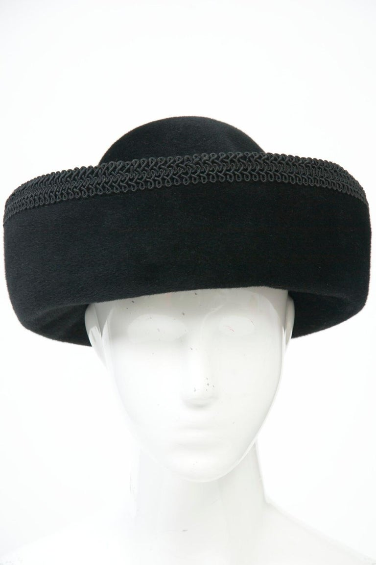 c.1960s hat by the Dachettes division of Lilly Daché, crafted of plush black velour felt and featuring a high round crown and deep rolled cuff, the latter trimmed with black braid. Interior circumference approximately 22