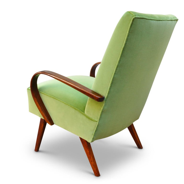 This small armchair is part of the Art Deco collection and is a modern approach to an evergreen design. It is manufatured using traditional techniques and natural materials. The armrests are made of solid bentwood painted a warm oak shade and the