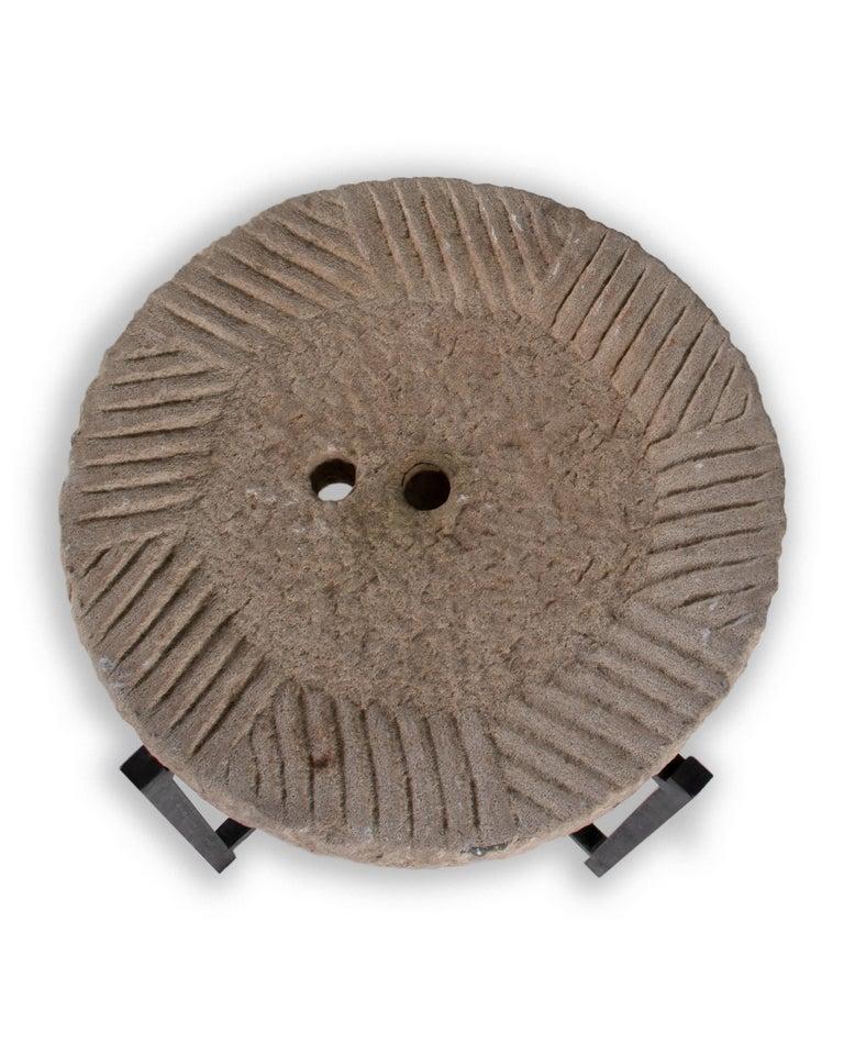 Limestone mill wheel on stand.