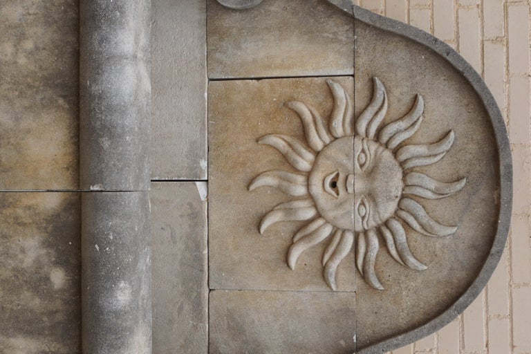 Here we offer a hand carved limestone wall fountain with a carving of the Sun with a human face. Louis XIV chose the sun as his emblem. The sun was associated with Apollo, god of peace and arts, and was also the heavenly body which gave life to all