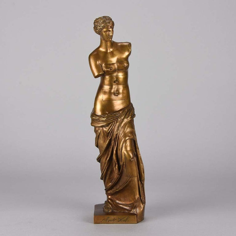 An excellent mid-20th century limited edition gilt bronze figure of Venus de Milo with Drawers by Salvador Dali – The figure of Venus de Milo incorporating drawer compartments to her head, breasts, torso and left leg to symbolize the memory and the