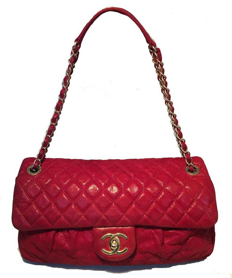 Chanel Shimmery Red Quilted Leather Pleated Front Classic Flap Shoulder Bag in very good condition. Shimmery red quilted calfskin leather exterior trimmed with matte gold hardware. Unique, limited edition pleated front design from the 2011