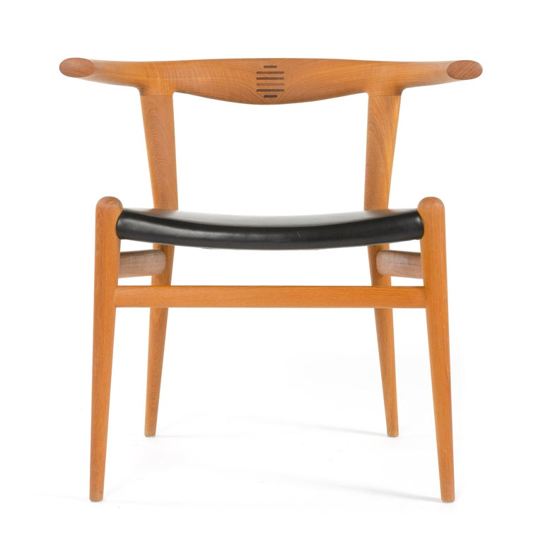 A very limited production teak Bullhorn chair by Hans J Wegner with a rosewood splined backrest and black leather seat. Available as a set of 8 chairs. Designed in 1961, limited production by PP Møbler in 2014.