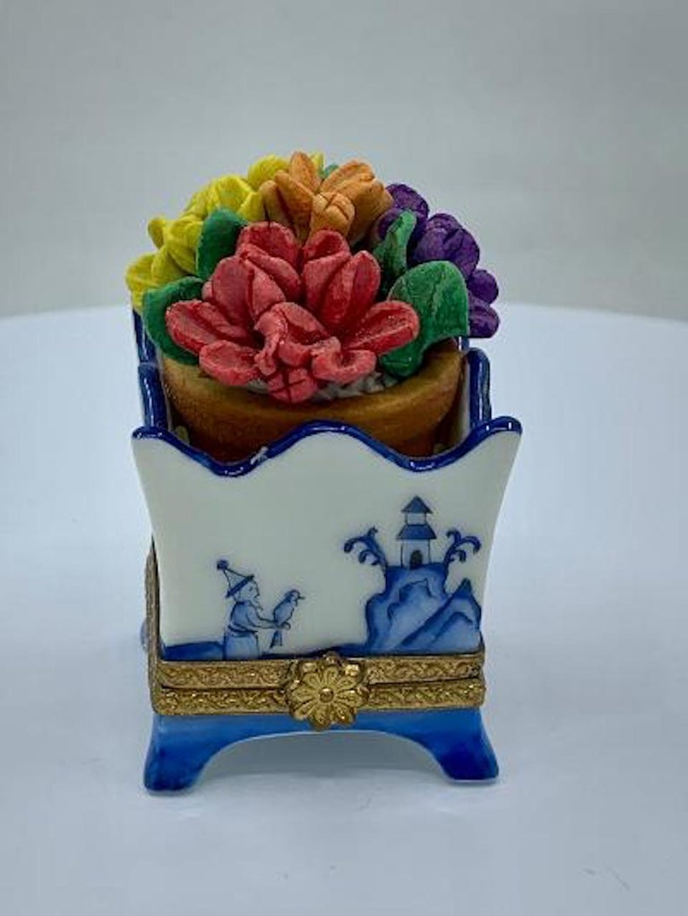 Collectible and very unique, Limoges porcelain miniature trinket box is handmade and hand painted in France and features beautiful multi colored three dimensional realistic flowers in a pot which sits on the top of the blue and white willow design