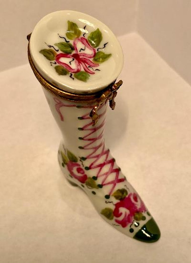 Very pretty Limoges porcelain old fashion Victorian style lace up boot shoe shaped trinket box is handmade in France and features a white background with skillfully hand painted clusters of deep pink roses, vining green leaves and a pink bow on top