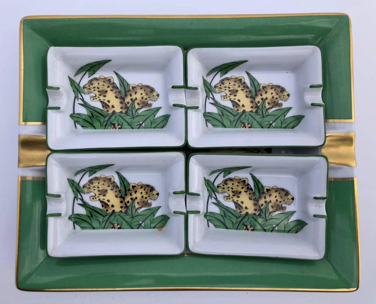 These handsome hand-painted Limoges porcelain ashtrays are in a vibrant green and gold color with gilded accents and a panther design. The largest tray in the set has a beautiful green border and share the same panther design on a white background.