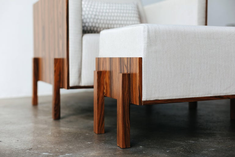 The use of fine woodwork at the sides and legs of the minimalist armchair adds to its sophistication. Both the wood and upholstery can be customized to order. The wood options are walnut, pau ferro, oak and ebony. The upholstery can be customized in