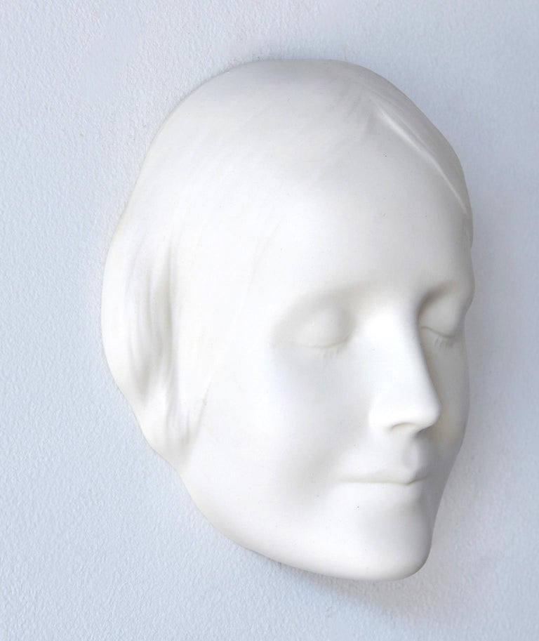 This bisque porcelain wall mask is of an anonymous woman who, in the 1880s, committed suicide by drowning by jumping into the Seine river in Paris. Her identity was never discovered, but her enigmatic facial expression and innocent, peaceful beauty