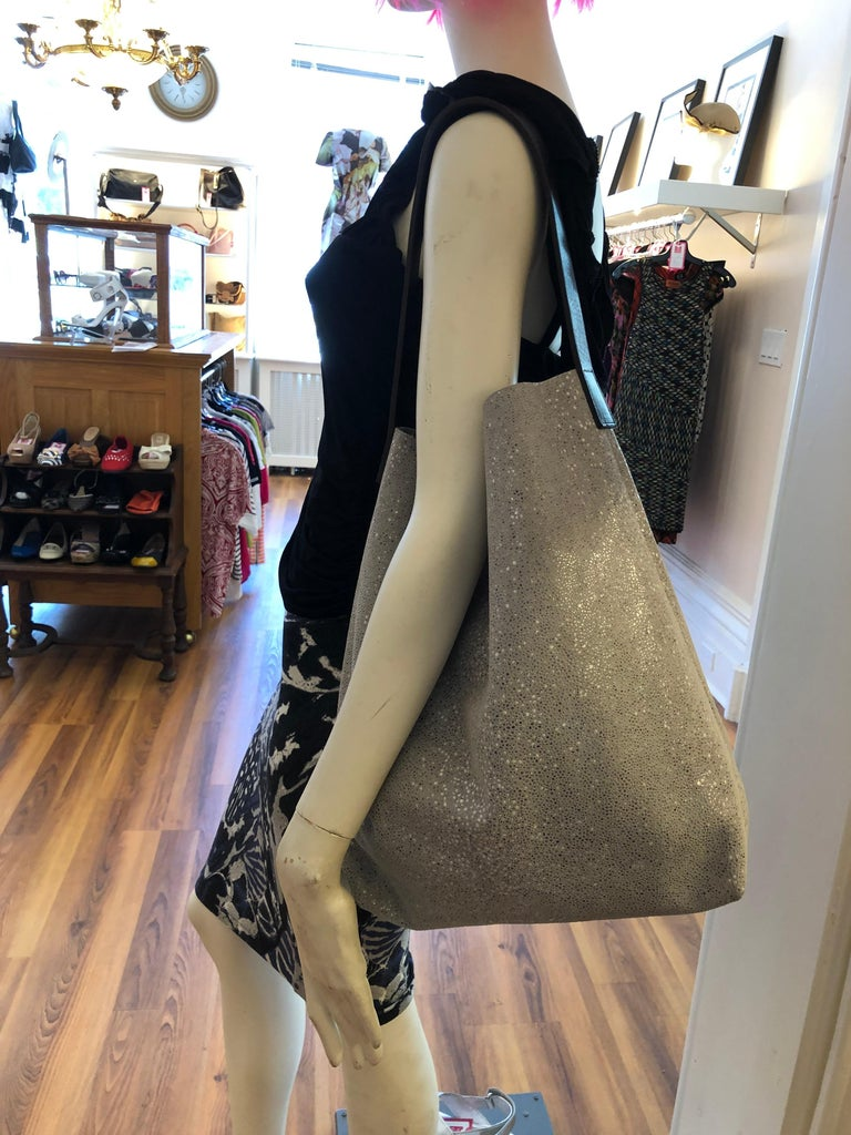 The Linde Gallery St Baths Hobo Bag is made in France of printed velvet leather with a leather shoulder strap (see 2nd picture). There is an inside zip pocket and a light resin finish which make this silver/grey colored bag sparkle.  The bag is