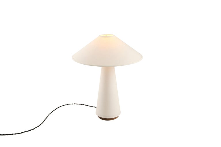 The Linden table lamp features a cream linen shade and lamp body, solid hardwood walnut base, and brass details. A study in duality, the piece explores the balance between soft, flowing fabric and structured, conical forms. Bulb sold separately.