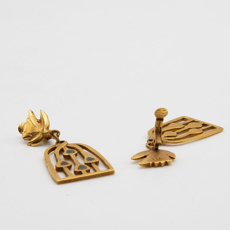 The earrings are composed of a gilded bronze structure, enhance with hot enamel. It is representing a bird carrying its cage. These pieces has been designed and produced in the beginning of the 1960s. Each is signed