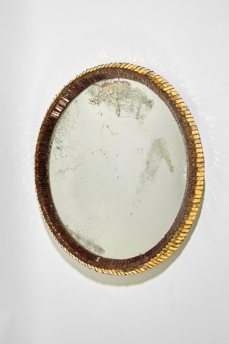 In talosel, slightly oval mirror, decorated with red chopsticks mirrors in an inner ring and encircled by an outer ring of gilded mirrors. Incised signature Line Vautrin on the back.