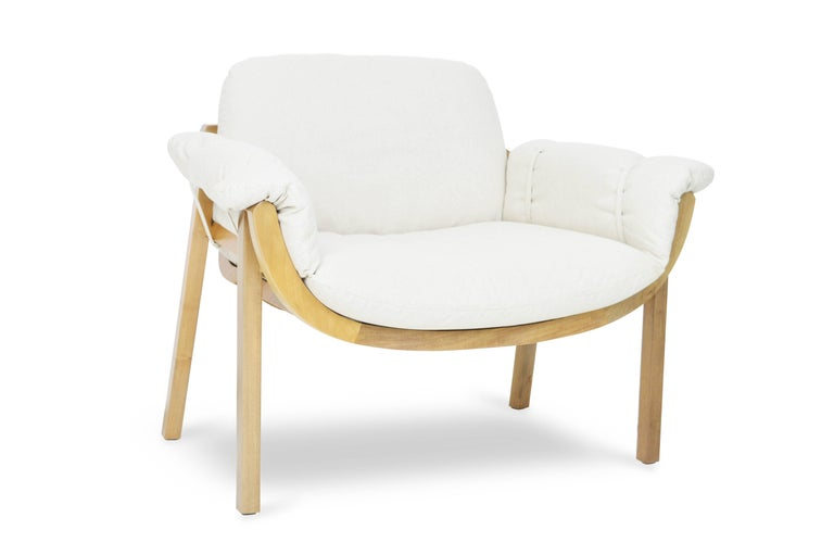 "It has as its main element the sequence of fitted in wooden ""ribs"" that define an organic form for the structure. This piece, made with precision by a computerized cutting machine gains the shape of a shell that shelters the upholstered section and"