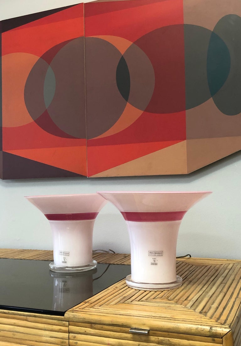 A pair of art glass lamps by Master art glass artist Lino Tagliapietra. White exterior with a light pink interior, raspberry band and clear base. Both are signed and dated 1982, also numbered 82 and 83 out of a limited edition of 100.