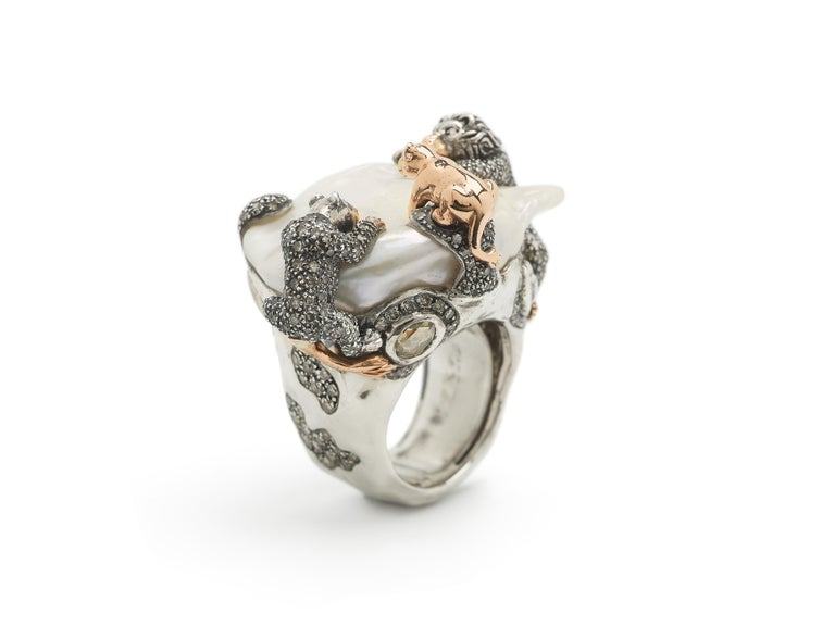 A luminous baroque pearl is home to a family of lions in this striking cocktail ring, part of Bibi van der Velden's Animal Collection. The sterling silver ring is set with three lions fashioned in 18k rose gold and sterling silver, with the design