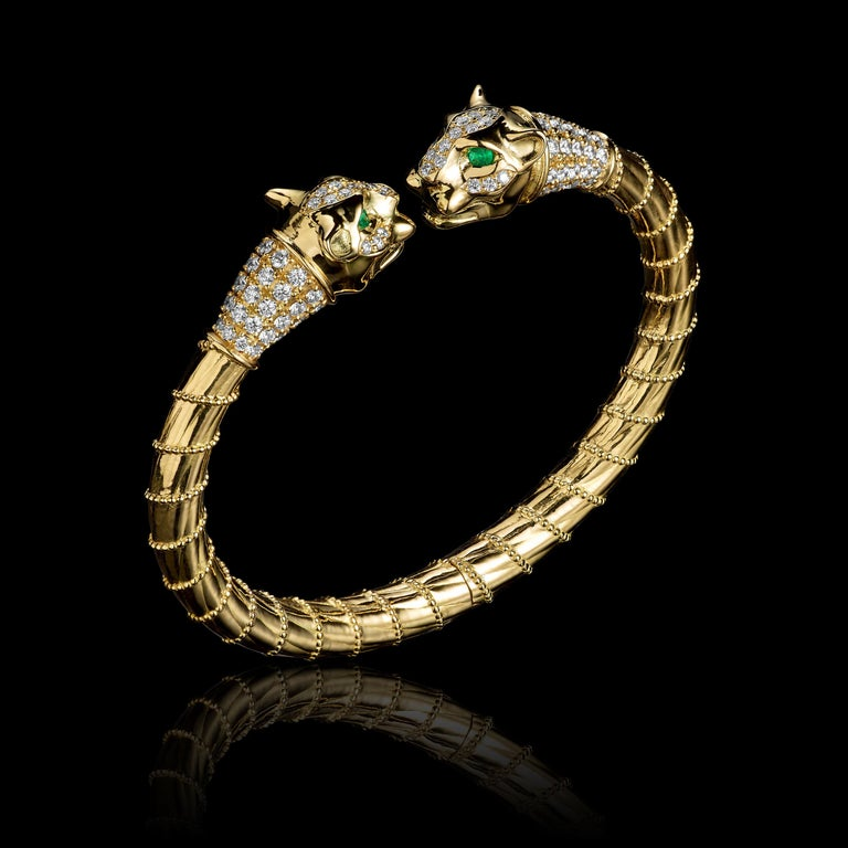 Lioness bracelet in 18K gold, with paved brilliant diamonds, and emeralds eyes. Detailed lioness faces, ornamental gold rope pattern, and hidden spring/hinge mechanism.  This bracelet features two lioness heads with emerald eyes and collars of