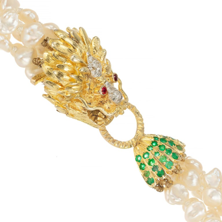 24 Inch 6 strand fresh water pearl necklace connected by a 14k yellow gold door knocker lion clasp with diamond nose and center of mane and ruby eye. The lion is grasping a round corrugated door knocker attached to an emerald accented pearl cup   28