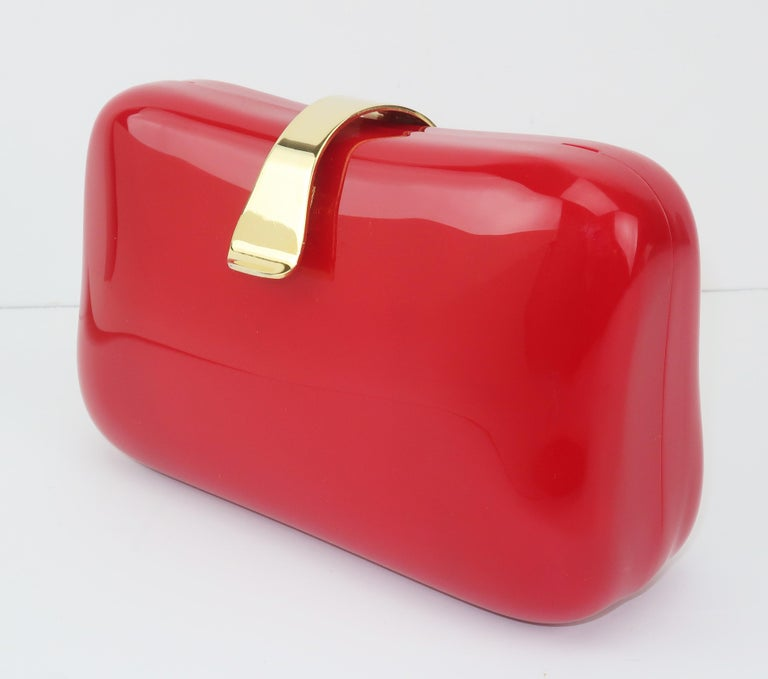 A 1980's lipstick red lucite handbag in a fun little box shape with a flip lock closure.  It sports a gold chain drop-in shoulder strap handle and features a red faille fabric lined interior with an open pocket.  As pretty to display as to carry!
