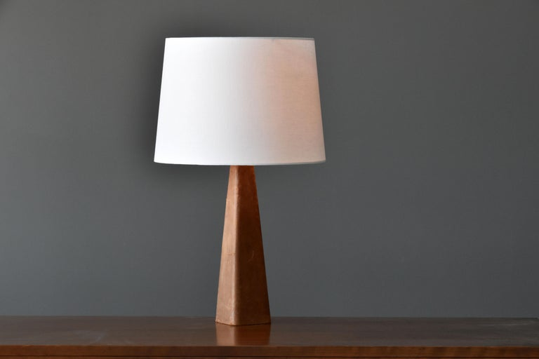 A table lamp designed by Lisa Johansson-Pape. Produced by Ornö, Finland in the 1960s.   Made of a solid block of wood covered in leather, fitted with a brass neck and fabric screen.   Other contemporary Scandinavian lighting designers include
