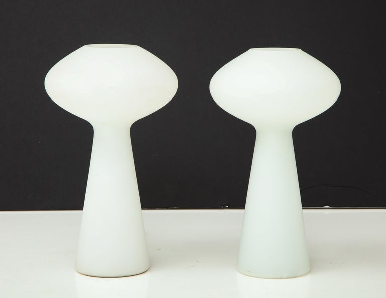 Pair of 1960s Lisa Johansson-Pape table lamps for Iittala. Comprised of a sculptural single piece of mold-blown, sandblasted and acid-etched opaline glass made in Finland, circa 1954. A contemporary of Paavo Tynell, the graceful yet simple forms