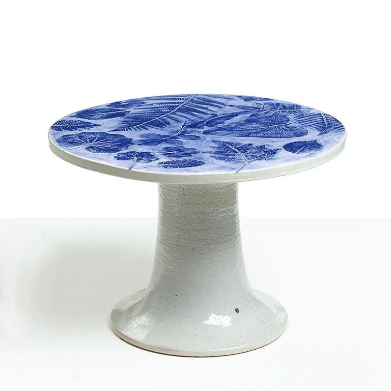 A small ceramic table designed by Lisa Larson for Gustavsberg Studio, Sweden in the 1960's. The table's top is decorated with fossil like impressions of various plant leaves and glaze in blue. The whimiscial column base has hand painted legs wearing