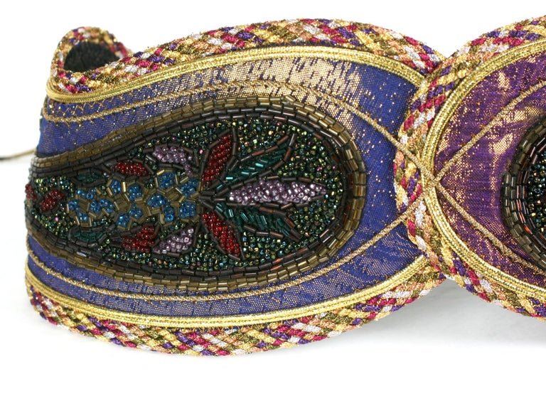 Lisandro Sarasola Extravagant Pieced Belt composed of paisley motifs which are overbeaded with lame cording, lame and applique. Bronze gold leather ties close the belt on the back. Wonderful colorations. Super striking, would enliven a monochromatic