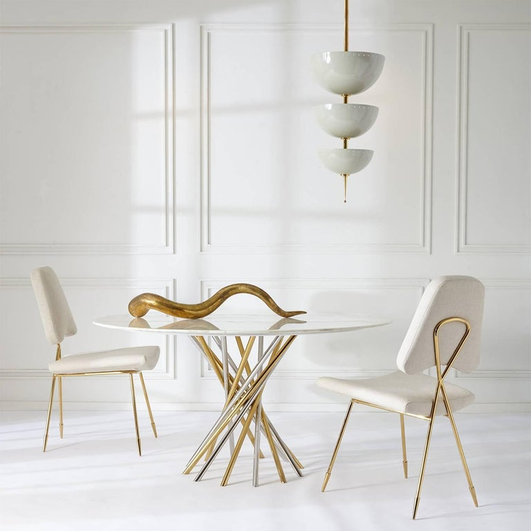 Magic mood. A polished brass stem supports three half spheres of ivory enameled metal in our Lisbon Pendant. Each metal bowl houses a double socket to provide soft uplight, creating a warm ambient glow. Fab in a foyer or over a petite dining table,