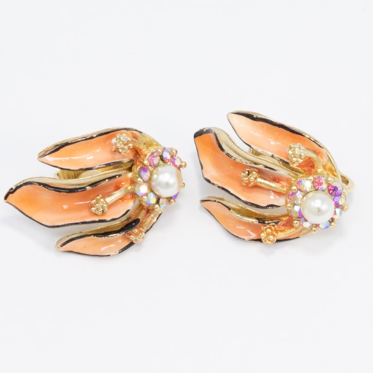 A pair of vintage clip on earrings by Lisner. Features gold-plated floral motifs painted with enamel and decorated with faux pearls & aurora borealis crystals.  Gold-plated.  Hallmarks: Lisner
