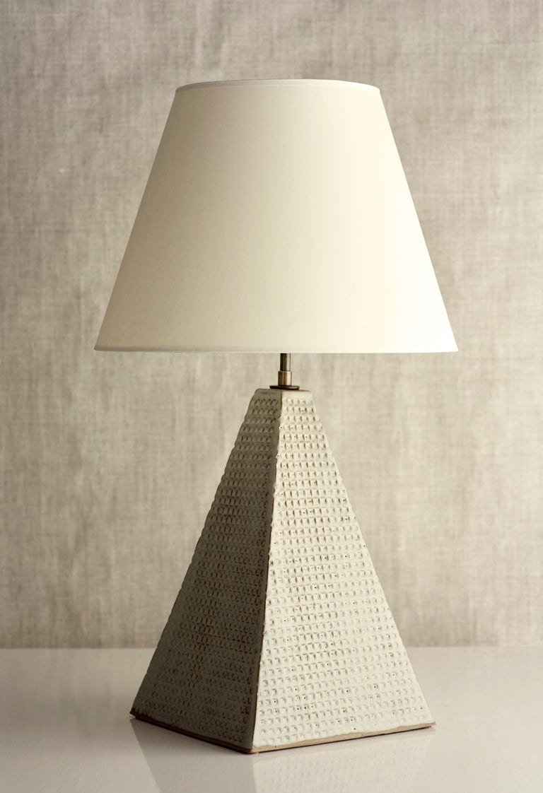Description  Handmade stoneware slab construction with waffle texture. Lamps are individually crafted and one of a kind.  Finish  Matte Ochre glaze with waffle texture. Antique brass fittings with braided black cloth cord and off-white paper