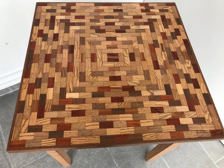 Newly refinished game or dining table has a mixed wood parquet top and oak base there is a small drawer in front with a brass knob.
