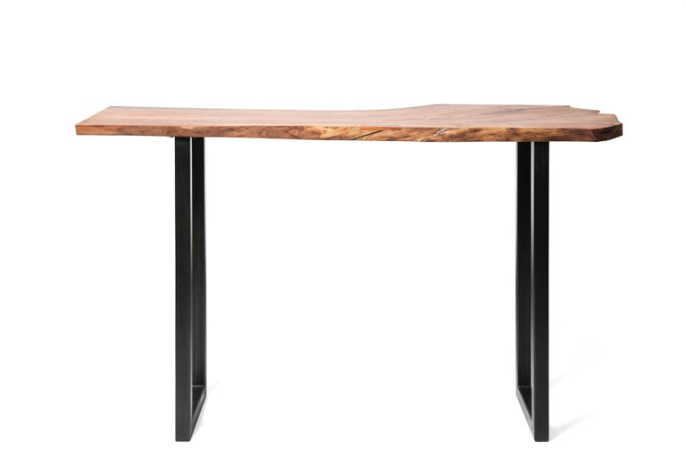 Our Live Edge Bar Table combines minimalist and rustic design elements.  The distinct grain of urban timber, locally harvested in Birmingham, Alabama, plays off the elegant and modern Sunrise base.  This bar height wooden table in pecan wood will