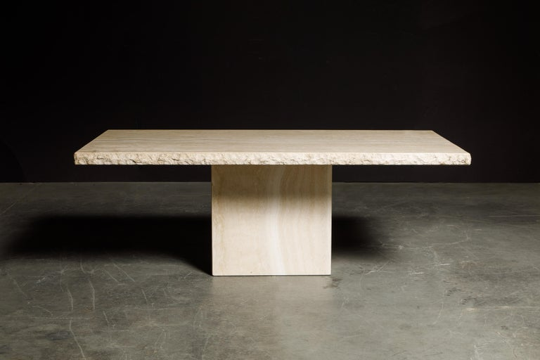 An incredibly stylish live-edge travertine dining table by Stone International S.p.A., this example is signed with the original Stone International label underneath the travertine top and inside the travertine base and dated July 30th 1990, the same