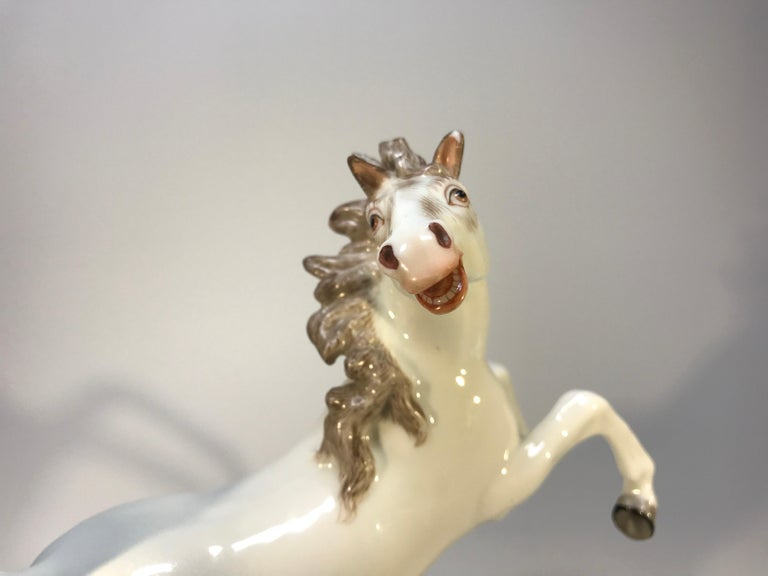 A charming and lively continental porcelain prancing horse. White glaze with hand painted detail. Exudes energy! Unknown origin, possibly Samson et Cie, 20th century Stamped with two blue crossed swords to rear of piece Measures: Height 6 inch,