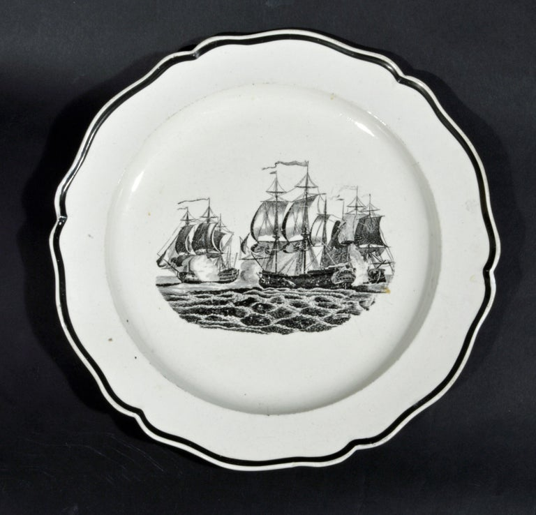 Liverpool pearlware plates decorated with ships, circa 1800. (NY7150B)  The Liverpool pottery pearlware plates with black rim are each printed with the image of a naval engagement.  Diameter: 9 3/4 inches  The Liverpool pottery pearlware