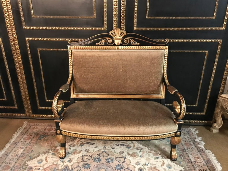 Very exact fine-carved sculpture made of solid, blackened beechwood. Poliment gold-plated. Scratched frame on sculpturally carved legs ending in claws. Armrests volute-shaped bent in swan head. High-right backrest frame crowned with Classic volute