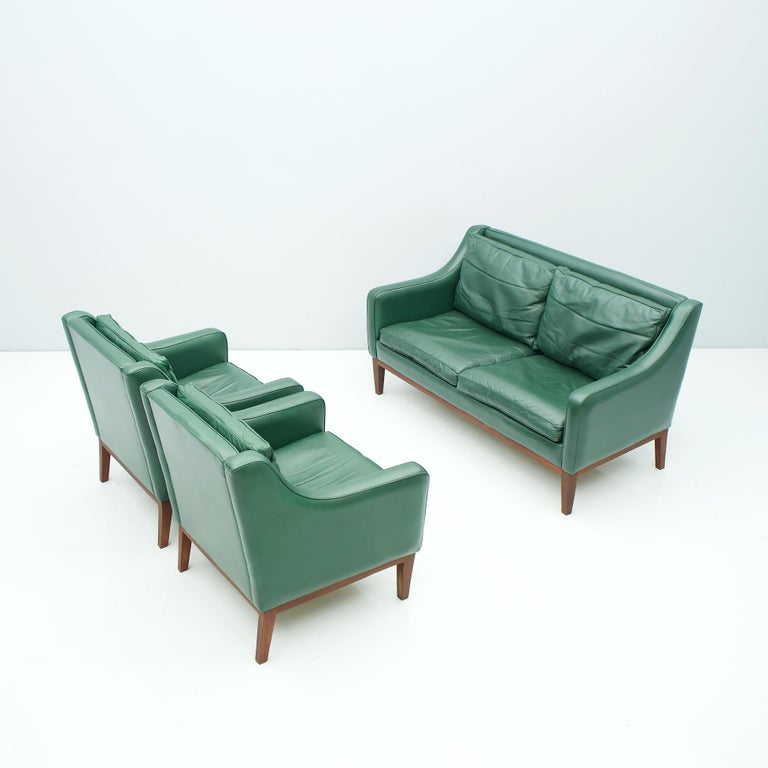 Beautiful living room set in green leather, Italy 1958. 2-seat sofa and two lounge chairs in green leather and wood frame (teak). The pillows are partly filled with down. The Set was bought in 1958. Origin Italy.  Measures:  H 76.5 cm, W 137 cm,