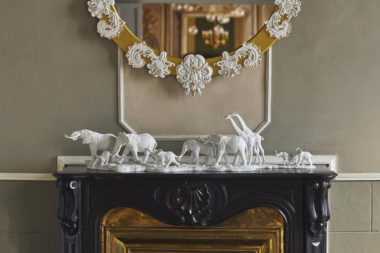 Sculpture in matte white porcelain animals from African savannah, adult female elephant that guides her group through a long path with an iroko wooden base. As an African proverb says: If you want to go fast, go alone. If you want to go far, go in