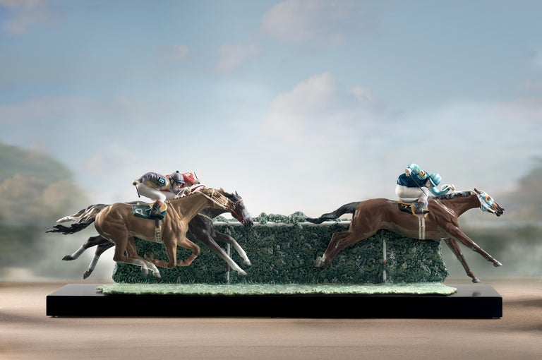 Glossy porcelain sculpture racing in the racetrack limited series represented by three horses with jockey of intense red and blue colors, combination of different glazes. Base included.