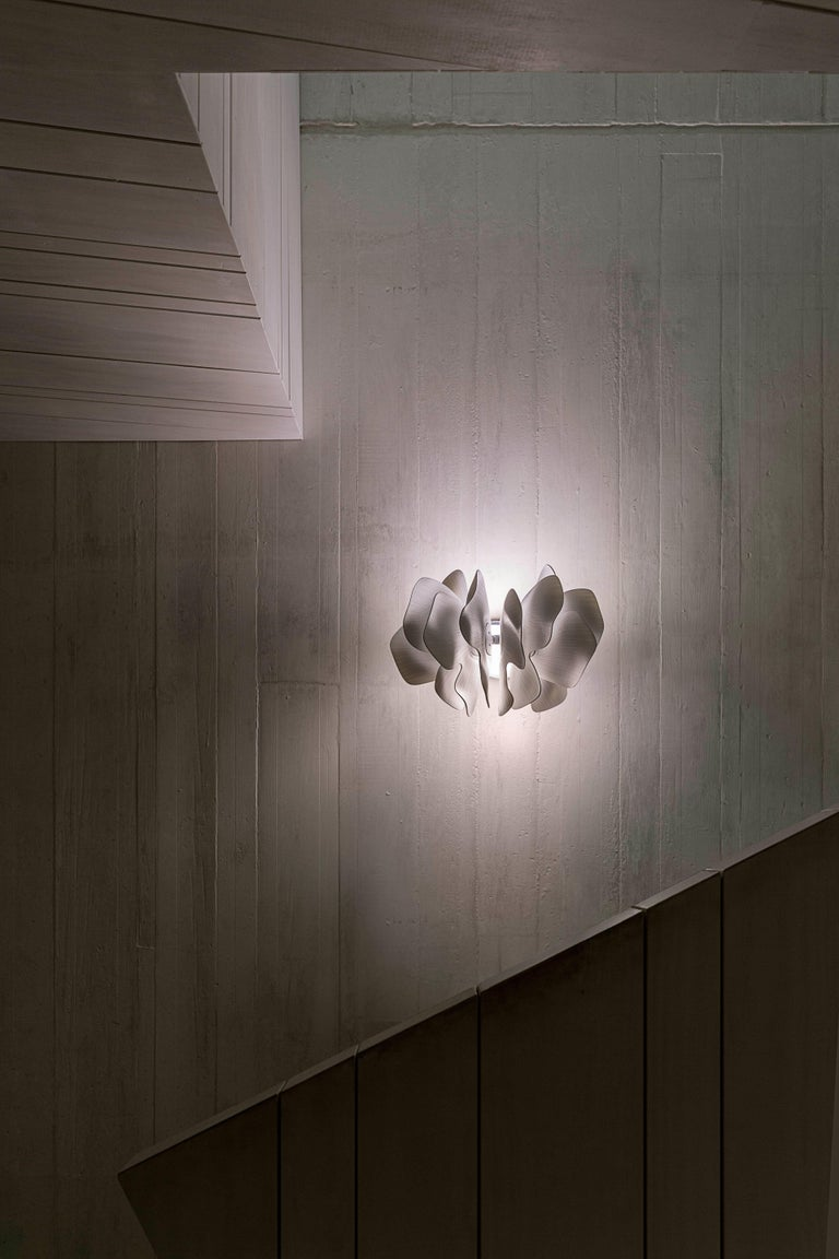 Porcelain wall lamp with a spectacular design inspired by the petals of a flower delicately swaying in the breeze. This work is part of the lighting collection created by Marcel Wanders in partnership with Lladró. A novel, contemporary design that