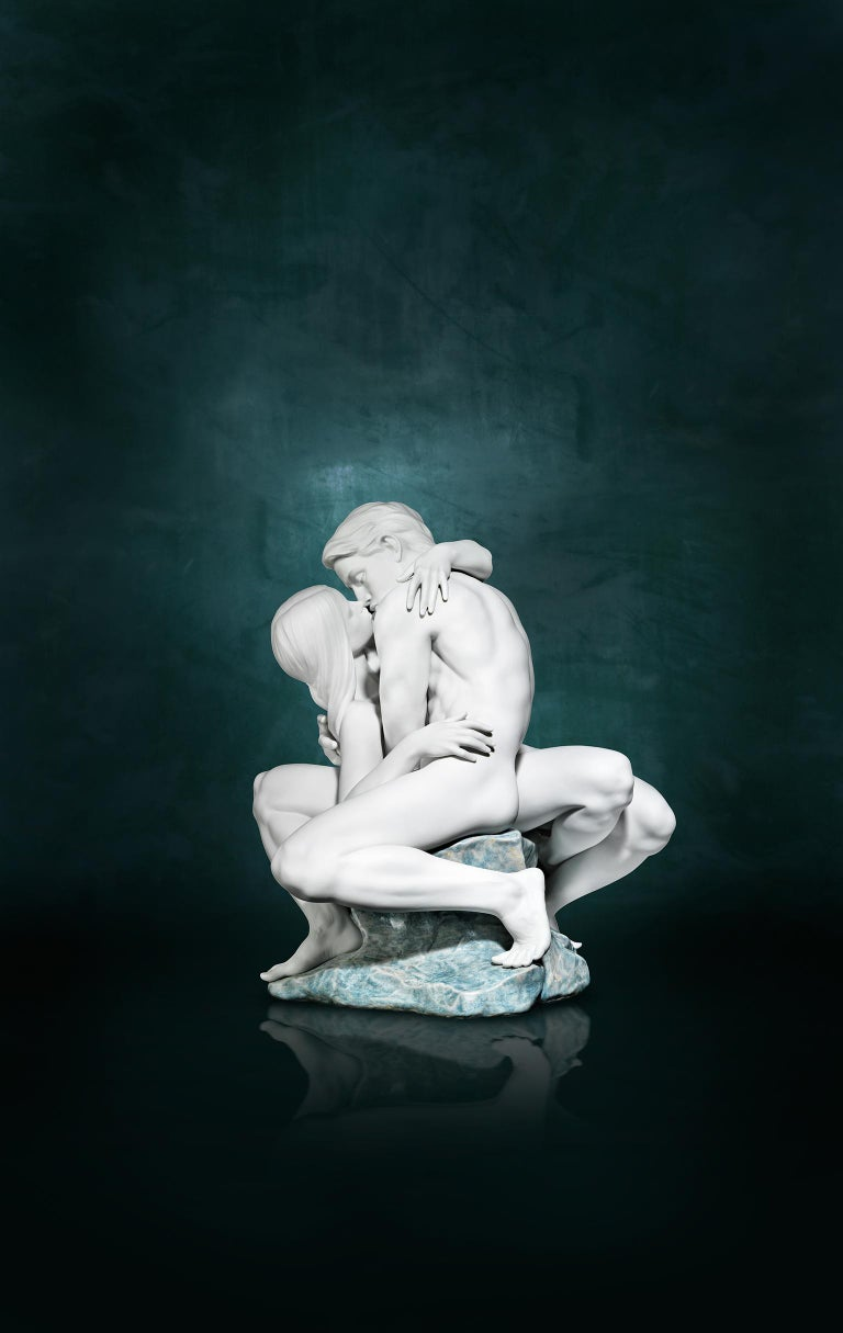 White satin-finished porcelain sculpture of a couple kissing sitting on a rock decorated with blue and green enamels. A couple's passion and love, captured as never before by Lladró. A piece of great sculptural prowess and technical complexity, in