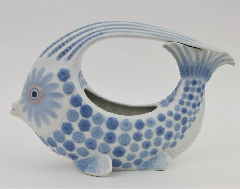A beautiful colorful porcelain fish figure centerpiece or vase designed by Vicente Martinez and manufactured by Lladró. It also can be used as a planter. The design and the blue tones make this centerpiece highly decorative. This piece is in mint
