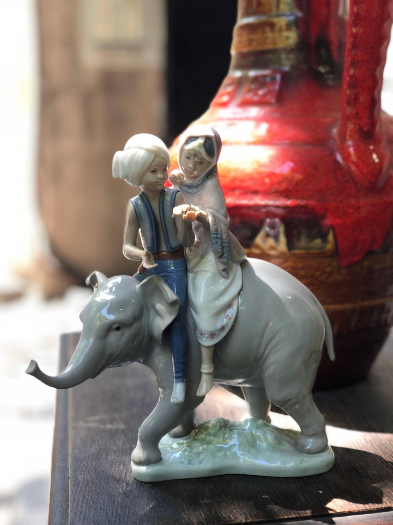 This Lladro piece is a porcelain figurine that depicts an young Indian elephant, upon which a pair of Hindu children sit. The glazed grey hues of the elephant's porcelain skin accentuates the intricate detailing and musculature of the largest land
